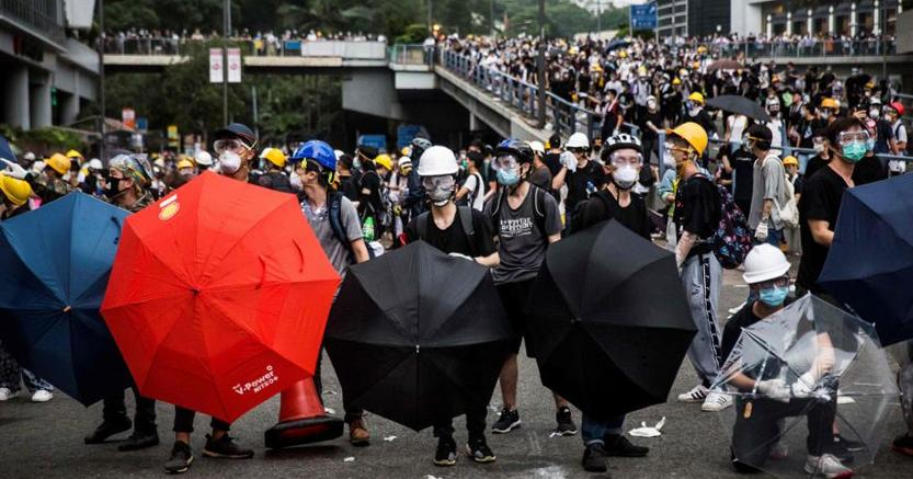 Manifestanti a Hong Kong si riparano con ombrelli dai gas lacrimogeni